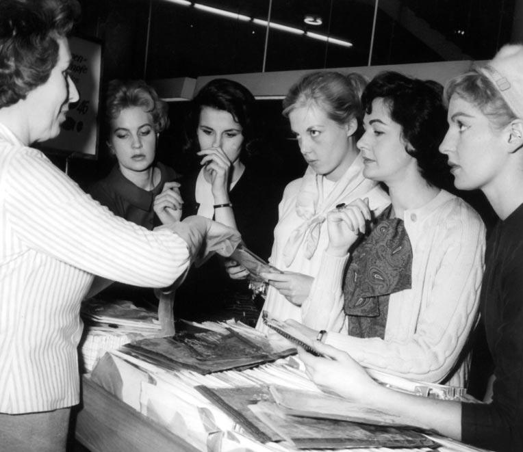 Cinco reinas de belleza de 1957, Miss Inglaterra (de izq. a derecha), Miss Australia, Miss Europa, Miss Francia y Miss Suecia, eligen medias durante un viaje por Alemania. Foto: Richard Kroll/dpa