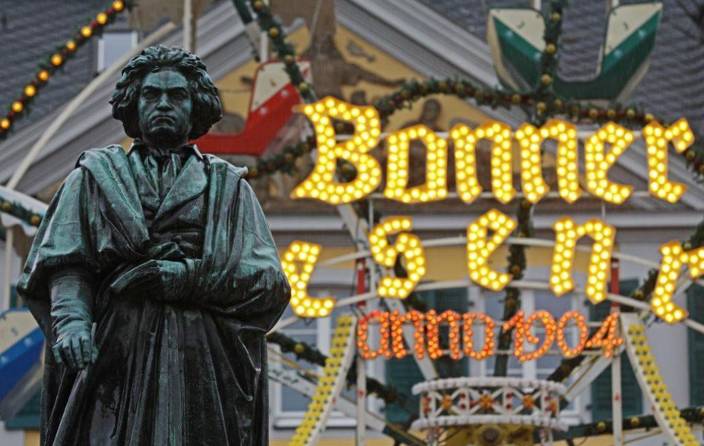 Una estatua del compositor Ludwig van Beethoven delante de la noria de un mercado de Navidad en Bonn, Alemania. Foto: Oliver Berg/dpa