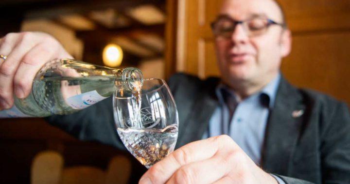 El sommelier de agua Martin Metzinger vierte agua mineral en un vaso. Foto: Tom Weller/dpa
