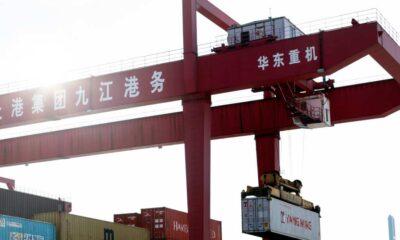 Imagen de una grupo portando un contenedor en un puerto en China